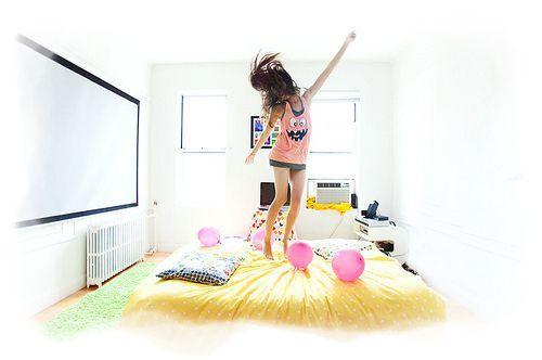 Chica saltando encima de la cama