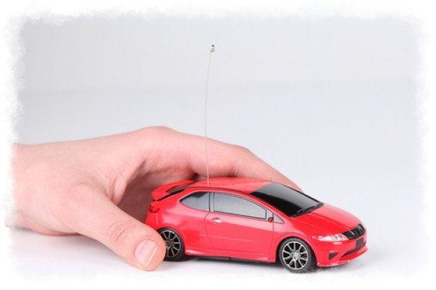 Mano conduciendo coche juguete